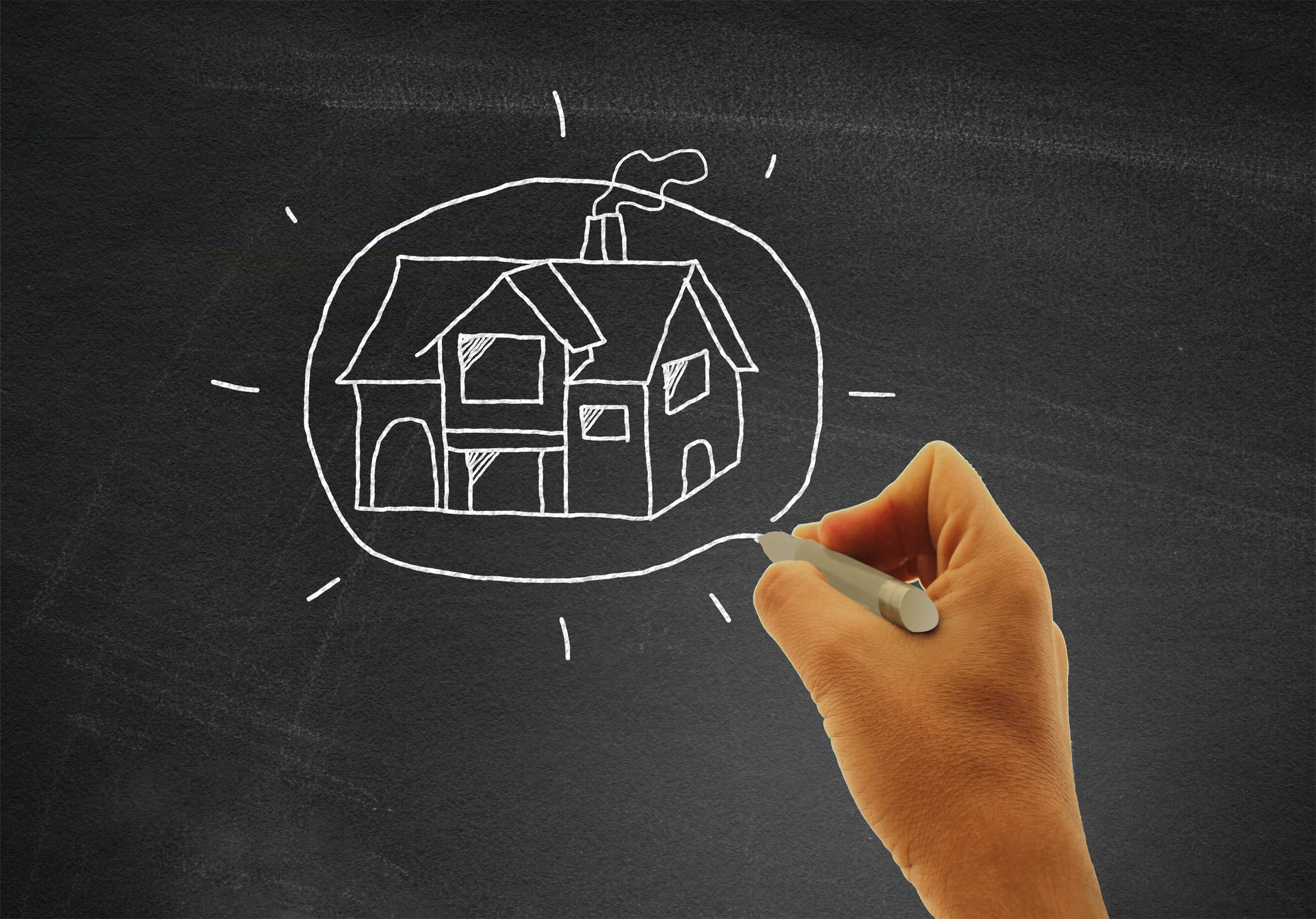 Hand drawing a house on blackboard - Real estate and housing con